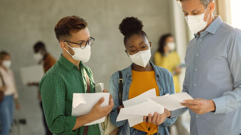 Two students and their teacher wearing face masks while having consultations at university hallway.