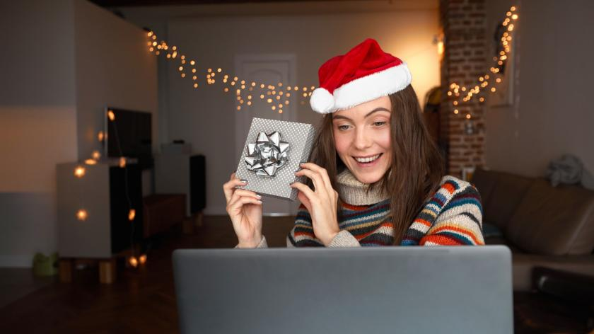 Delighted female in Santa hat smiling and showing gift box to online friend while celebrating Christmas at home