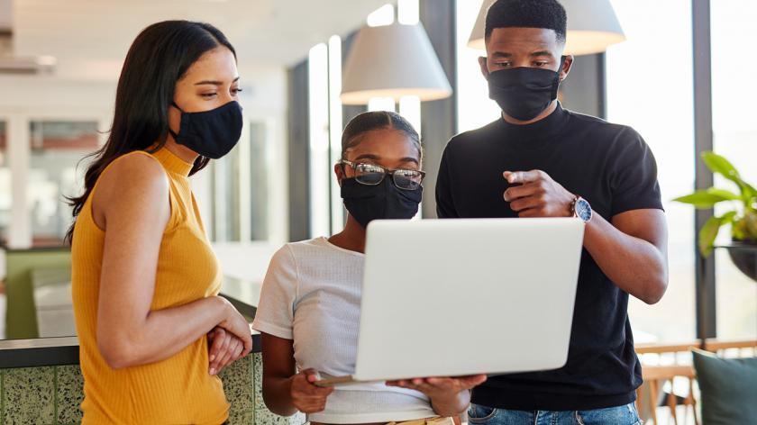 Shot of a group of masked young businesspeople using a laptop in a modern office