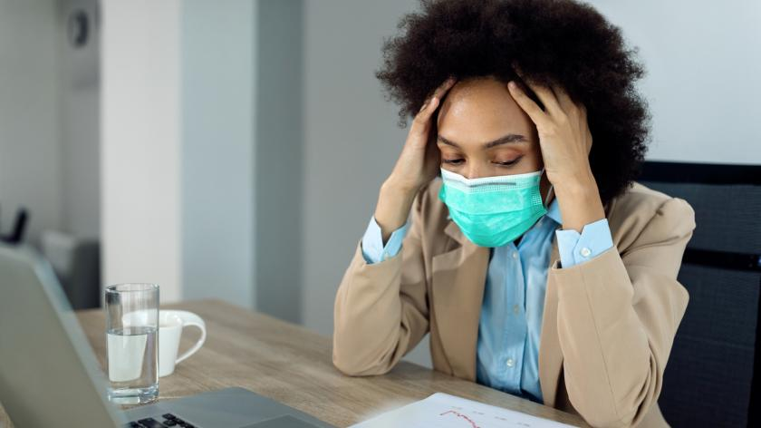 anxious woman wearing mask at her desk