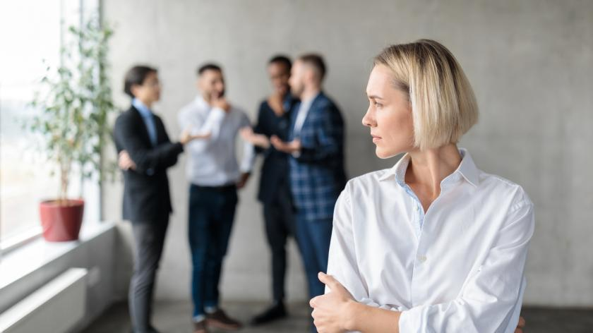 Male Coworkers Whispering Behind Back Of Unhappy Businesswoman