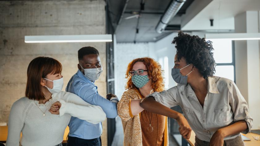 Happy businesspeople with face masks elbow bumping at the office