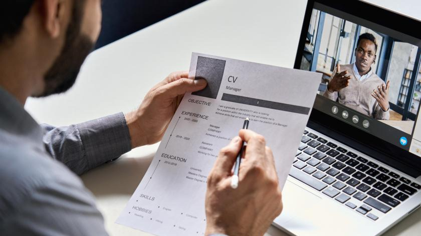 hr, recruiter or employer holding cv having online virtual job interview meeting with candidate on video call. Distance remote recruitment conference chat. Over shoulder view.