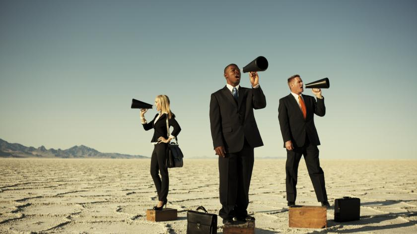 A male businessman leads his team in voicing their business message.