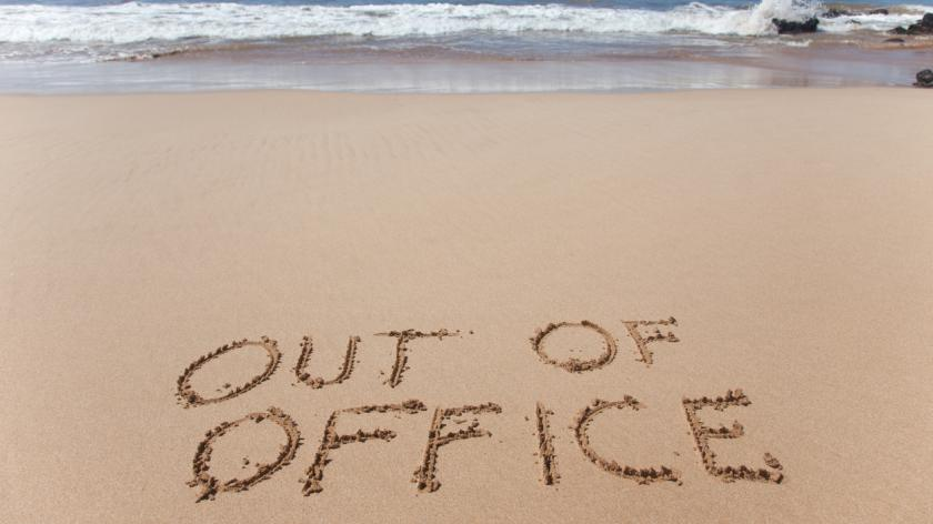 Out of office written in the sand on a beach