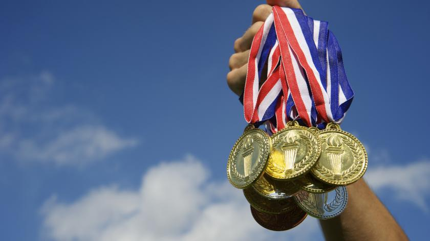 Hand holds up a bunch of gold, silver, and bronze medals in bright blue sky