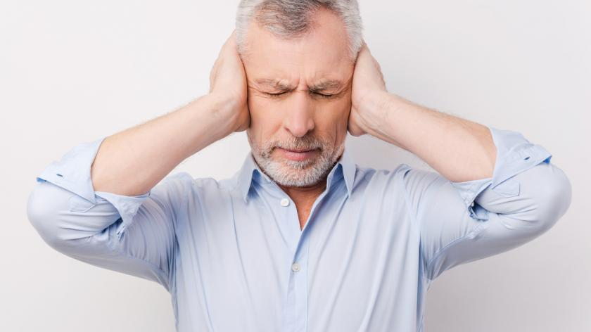 older man covering his ears