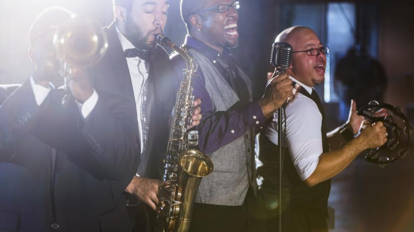 A jazz band performing at a nightclub. The four male musicians are standing together, playing a trumpet, saxophone, and tambourine.