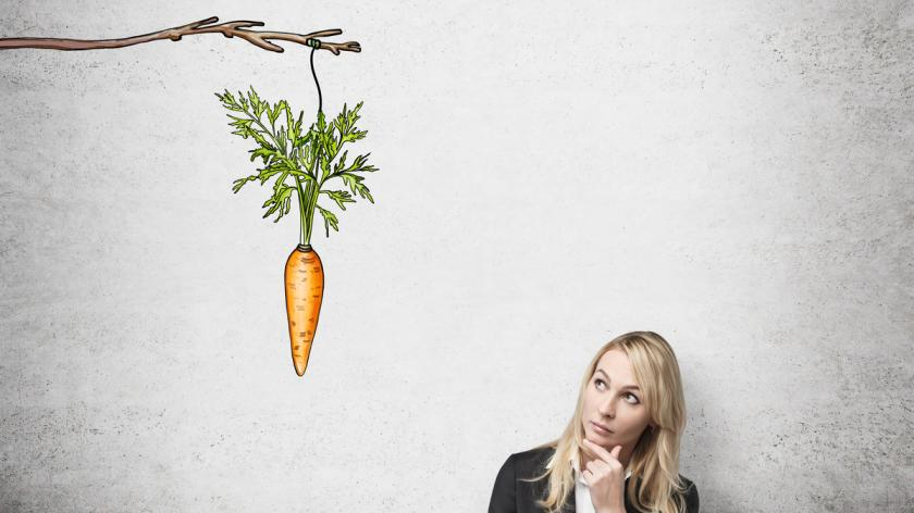 woman with her hand on chin looking up at a painted carrot tied to a branch. Concrete background. Front view. Concept of reward.
