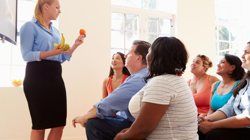 group of people People Attending Diet Club Listening To Instructor Holding Different Fruits