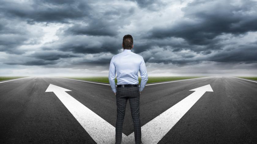 businessman standing at crossroads