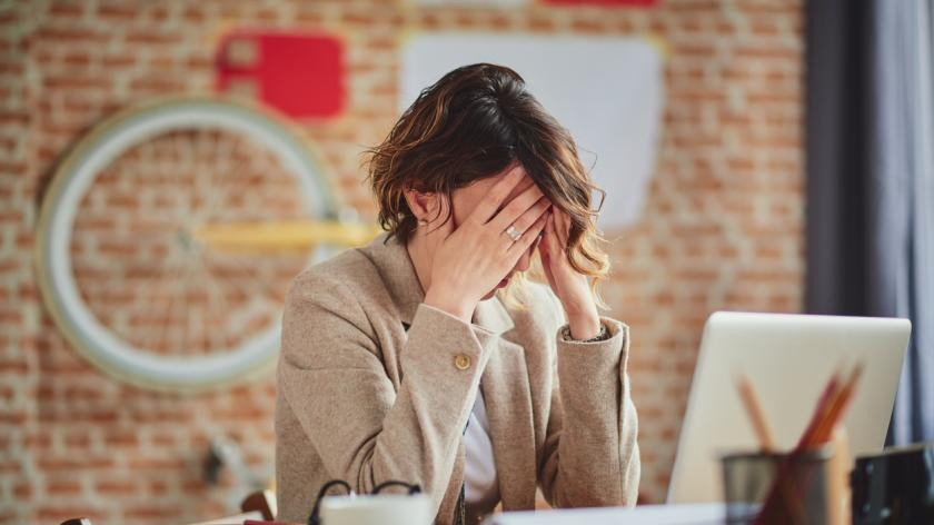 Women with head in hands at work