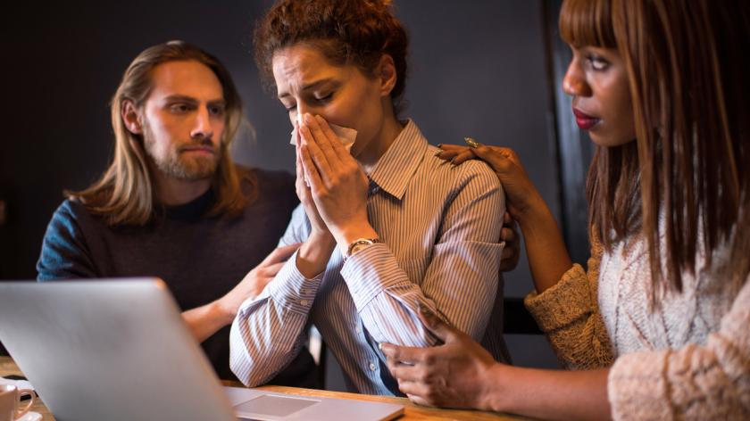 Two business colleagues comforting their depressed female coworker who is crying.