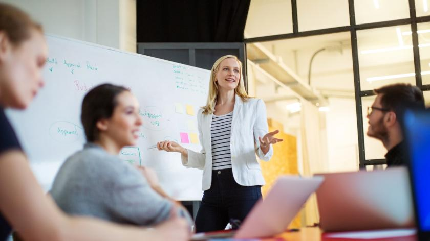 Businesswoman giving presentation on future plans to colleagues