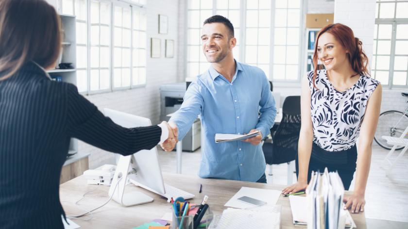 woman shaking hands with interviewers in an office
