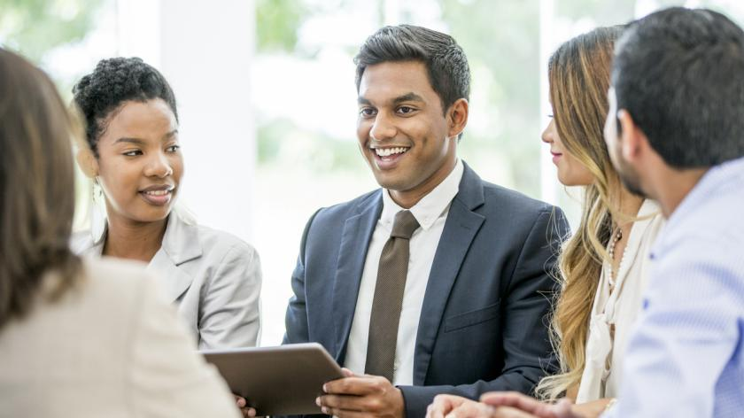 A multi-ethnic group of business professionals are working together at the office.