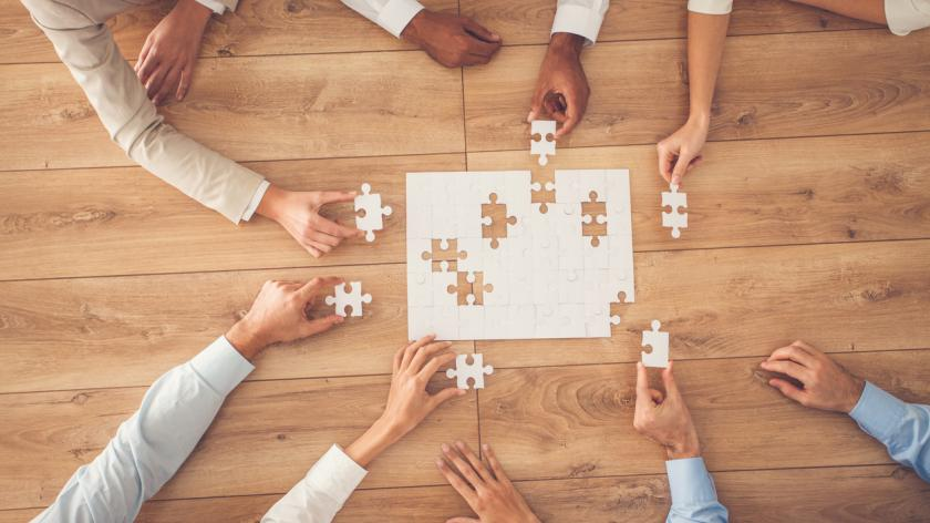 Business people sitting at office desk, putting puzzle pieces together, finding solution