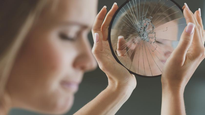 woman with imposter syndrome looks at herself in a cracked mirror
