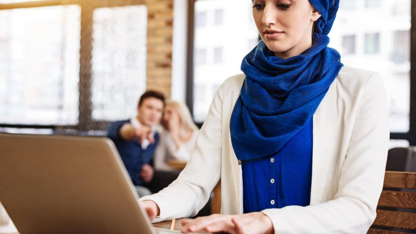 Muslim woman working at desk while colleagues whisper behind her