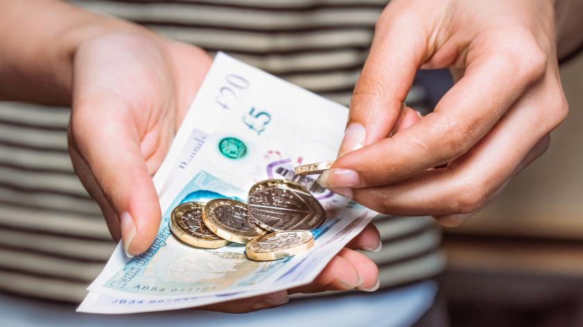 hands paying with UK currency