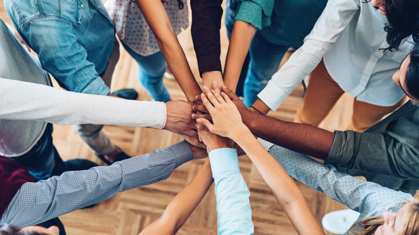 diverse group of colleagues linking hands