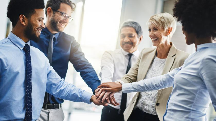 employees linking hands in a meeting