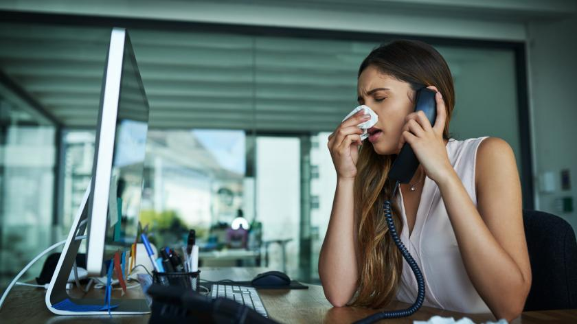 woman blowing her nose at her work desk