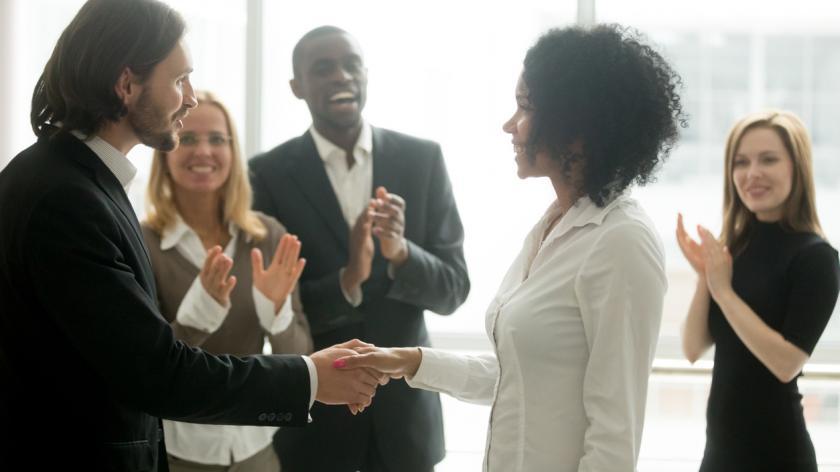 Grateful boss handshaking colleague