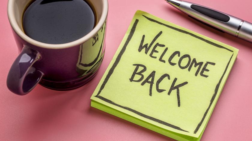 welcome back - handwriting on a sticky note with a cup of coffee