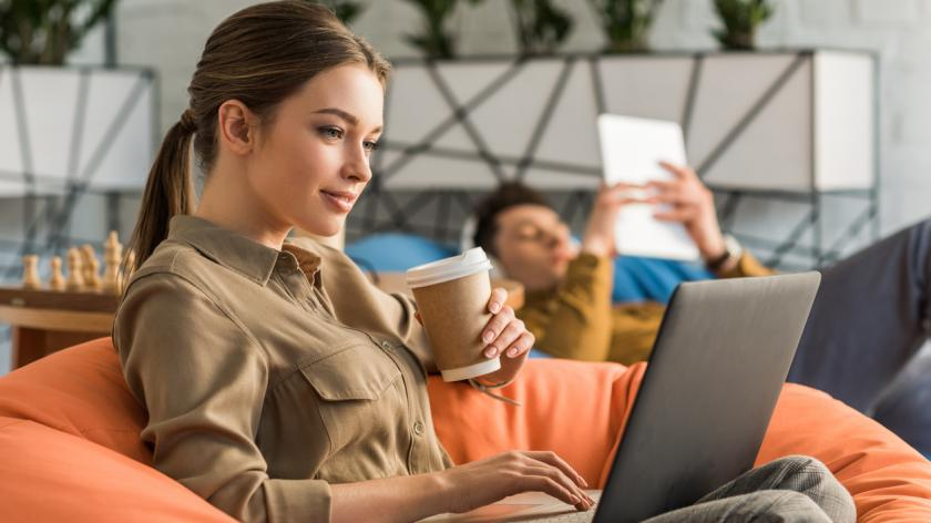 Young woman drinking coffee and working with laptop while sitting in bean bag