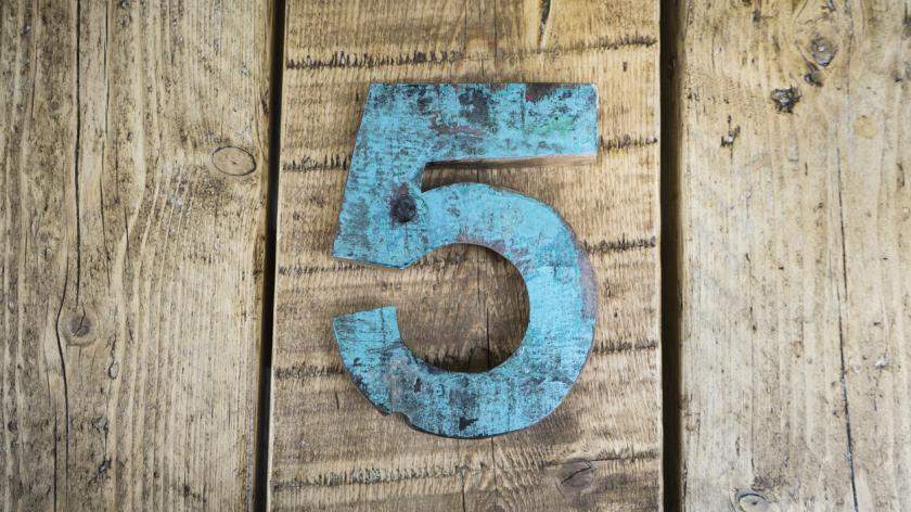 Number five on wooden background