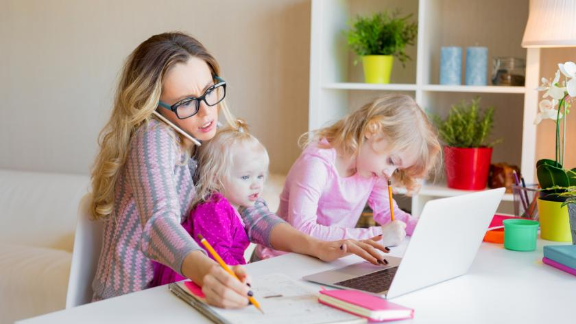 woman caring for two children while working at laptop