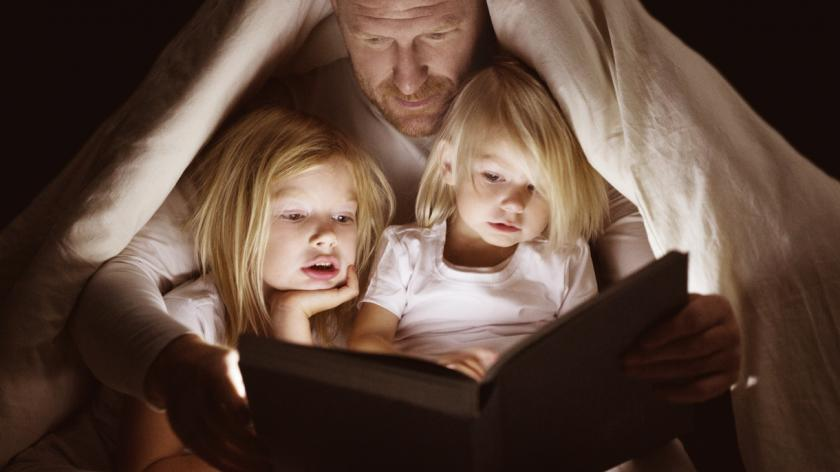 Father and daughters reading book at bedtime