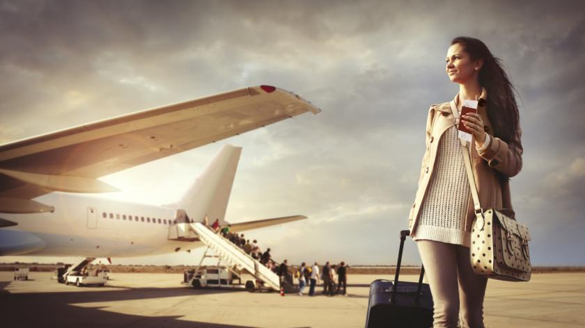 Young woman with suitcase arrived at the airport
