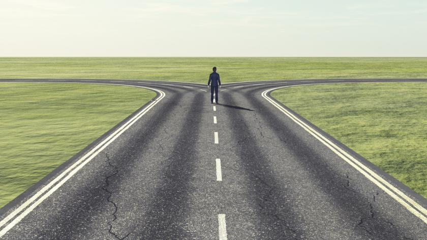 Businessman in front of two roads: which path?