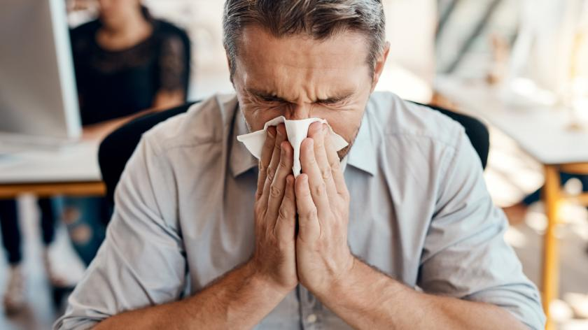 Contagious infection at work - man sneezing