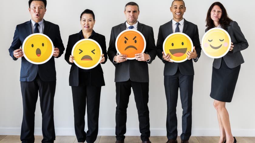 business people holding emoji symbols
