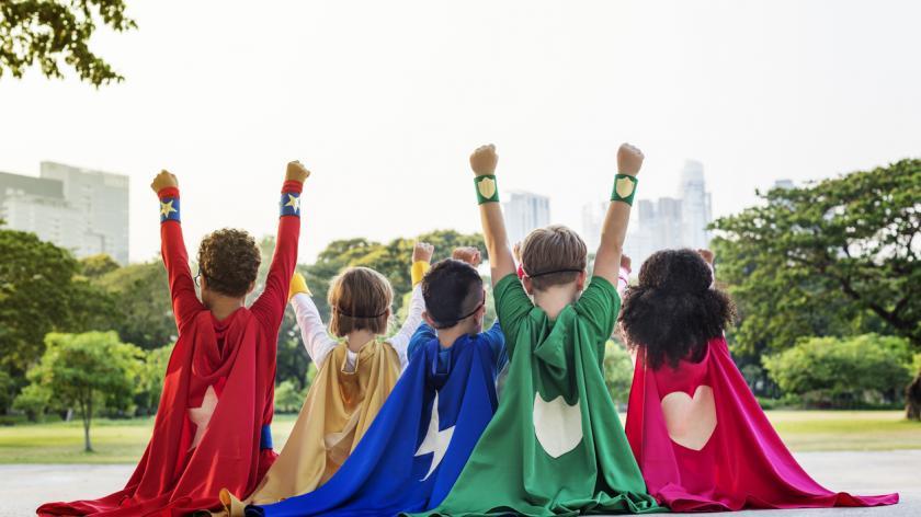 happy children dressed as superheroes