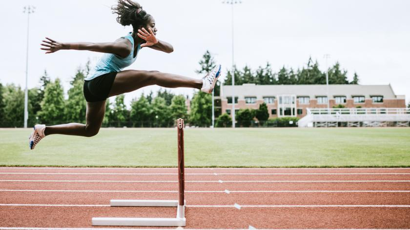 Woman Athlete jumping over hurdle