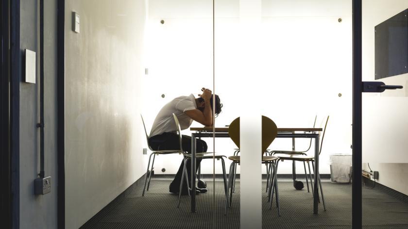 Man stressed at work in meeting room