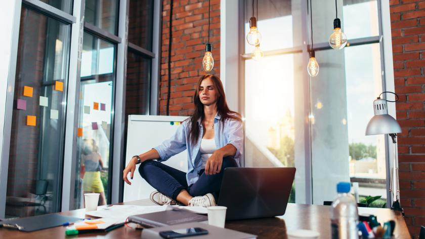woman meditating on office desk