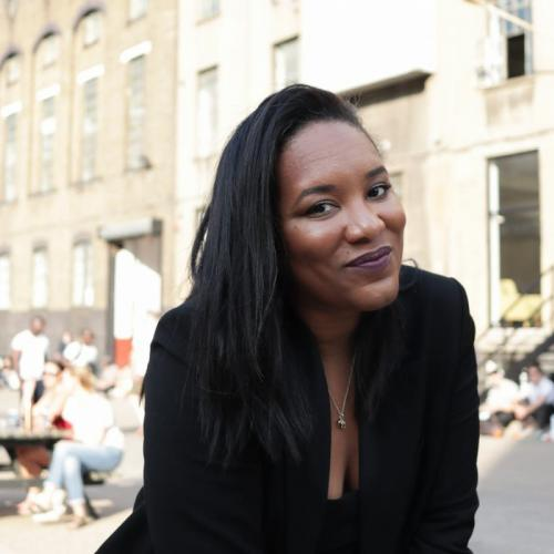 A darker toned lady sitting on a wall, smiling